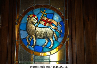 Florence, Italy - 5.28.2011: Stained glass Agnus Dei or The Lamb of God in Duomo cathedral,title for Jesus in Gospel,a standing haloed white lamb holding pennant with red cross on white background