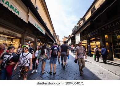 Florence Italy - Apr 2017: Visiting the gold, jewelry, and luxury stores on the famous Ponte Vecchio bridge crossing over Arno river