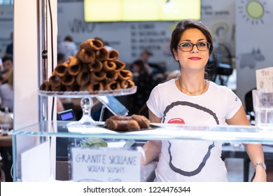 Florence, Italy - August 30, 2018: Woman, female seller, cashier in Firenze Mercato Centrale, central market selling cannoli, standing, smiling, happy