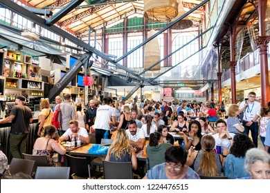 Florence, Italy - August 30, 2018: Interior, inside, indoor of Firenze Centrale Mercato, central market with crowd of people sitting on chairs by tables, eating food, drinks from cafes, restaurants