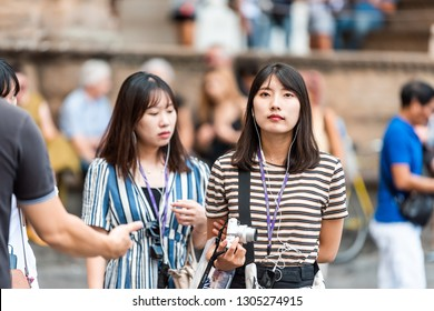 Florence, Italy - August 30, 2018: Closeup portrait of young Asian woman face walking on street in historic city listening to tour guide with camera and headphones