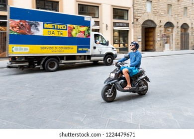 Florence, Italy - August 31, 2018: Panning shot of young Italian man riding, driving, moving on vespa scooter, motorcycle on street of Firenze, Italian city
