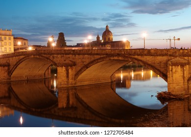 FLORENCE, ITALY - AUGUST 7, 2018: Night view to Ponte alla Carraia bridge and the church San Frediano di Cestello. The current bridge was completed in 1948 after the blowing up during WWII