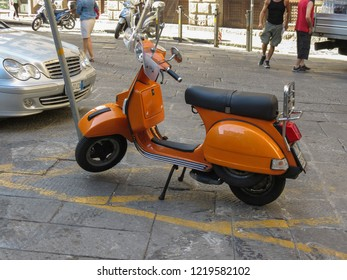 FLORENCE, ITALY - CIRCA JULY 2016: orange Piaggio Vespa motorbike parked on the street