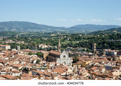 Florence, Italy cityscape showing the surrounding hills and the ornate marble facade of Santa Croce Church.  Copy space in sky if needed.