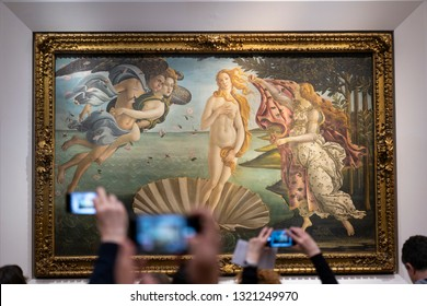 FLORENCE, ITALY - FEBRUARY 18, 2019: Tourist hands lifting cell phones to take picture of famous Birth of Venus painting in museum