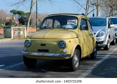 FLORENCE, ITALY - February 24, 2019: A vintage, cream yellow Fiat 500 parked on the street near the center of Florence.