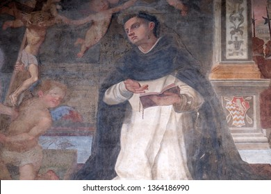 FLORENCE, ITALY - JANUARY 09, 2019: The lunette of one of the side doors depicting St. Thomas Aquinas, detail of the facade of the Church of Santa Maria Novella in Florence, Italy
