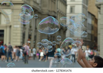 FLORENCE, ITALY - JULY 02, 2017: happy man entertaining tourists and citizens with flying soap bubbles in the old center of Florence. People watching city perfomance. Street funny show