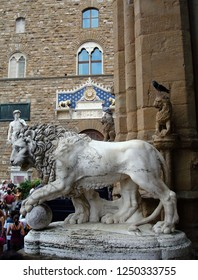 FLORENCE, ITALY - JULY 20, 2014: Medici Lion and Perseus statues in Loggia dei Lanzi and Palazzo Vecchio on Piazza della Signoria-Square of Signoria,numerous tourists, sunny autumn day.