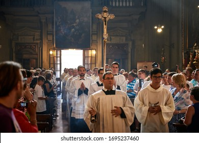 FLORENCE, ITALY - JULY 20 2019: Priests walk in San Firenze Church holding a high cross, adepts occupy the seats on both sides of the main nave