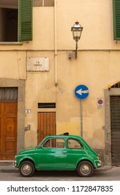Florence, Italy, June 12, 2015: Small vintage green motor vehicle parked outside yellow building, Florence, Italy