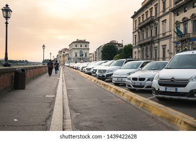 Florence, Italy - June 12, 2018 : Cars parking along side of Arno River, in the historical Old Town of Florence in golden light. Tuscany, Italy.