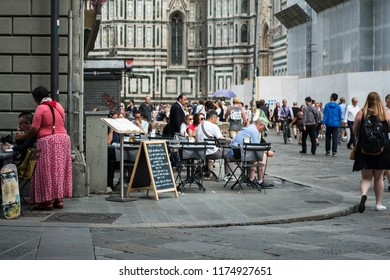 Florence, Italy - June 13, 2018 : View of tourists walking and enjoy eating  near Duomo Florence Cathedral (Santa Maria del Fiore). Florence is one of the most romantic destinations in Europe.