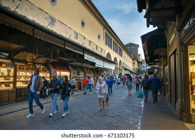FLORENCE, ITALY - JUNE 3, 2017: tourists near shops on Ponte Vecchio (Old Bridge) in Florence in evening. The Ponte Vecchio is medieval stone bridge noted for still having shops built along it