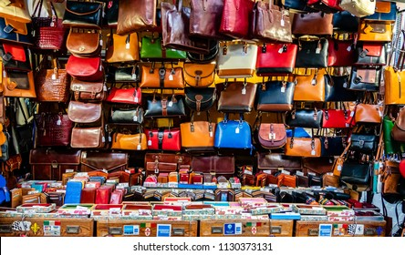 Florence, Italy - June 8, 2018: Florence is well known for its leather goods, including these colorful leather purses and wallets on display for sale at the outdoor Lorenzo Market.