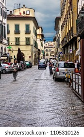 Florence, Italy - June 9, 2016:  Pedestrians along a narrow cobblestone road in the city of Florence, Italy.