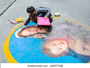 "FLORENCE, ITALY - MARCH  14, 2015: A street artist draws ""Madonna and Child""   painting, on asphalt on March 14, 2015 in Florence, Italy."
