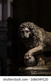 """Florence/ Italy - March 20 2020: Piazza della Signoria. Loggia dei Lanzi, Flaminio Vacca, """"Lion"""". The city empty because of the Coronavirus."""