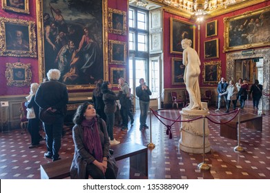 Florence, Italy - March 3, 2019: Visitors admire famous masterpieces, paintings and statues, in a room of the Palatina Gallery Museum, in Florence.