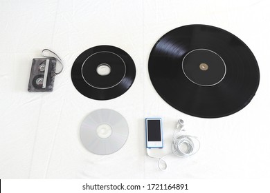 Florence (Italy) May 01 2020 - Tape cassette, 45 rpm record, 33 rpm vinyl record and music CD on a white background.