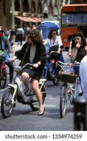 FLORENCE, ITALY - MAY 14, 1999- Young woman on vespa motorbike in traffic in central Florence, Italy