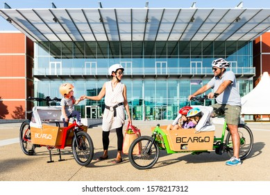 florence, Italy - May 15m 2019 - happy family with 2 children moving around city with cargo bike