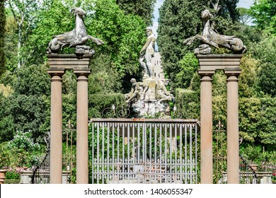 Florence, Italy - May 16, 2019: View of the Perseus and Andromeda Fountain through the Capricorns gate, symbol of the Medici family, the beautiful Boboli gardens