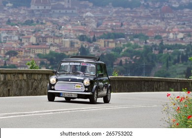 """FLORENCE, ITALY - MAY 19: Mini Cooper along Via Bolognese during the 1000 miles on May 19, 2013 in Florence, Italy . """"Mille Miglia"""" is a car race attempted by many celebrities"""