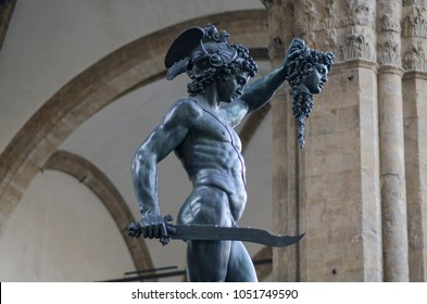 FLORENCE, ITALY - November 15, 2017: Perseus with the Head of Medusa, under Loggia dei Lanzi against Palazzo Vecchio