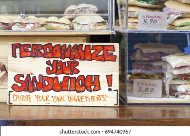 Florence, Italy: November 20, 2016: A street cafe advertises its sandwiches with a slogan to personalise your sandwich. Sandwiches with prices and company logo and name are on display.