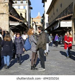 Florence, Italy: November, 2016: Two people hug on the famous Ponte Vecchio bridge while other tourists walk by. Ponte Vecchio is a Medieval closed-spandrel segmental arch bridge over the Arno River