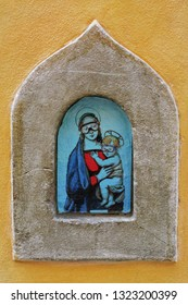 FLORENCE, ITALY - NOVEMBER 8, 2018: The Madonna and Child in diving masks - modern street art in medieval wine portal (Buchette del vino)