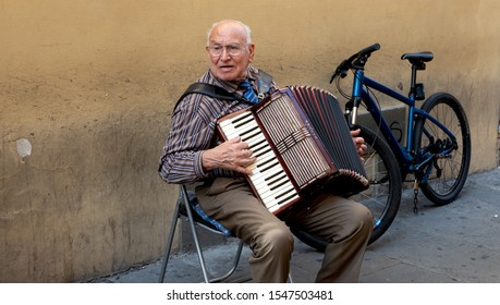 Florence, Italy, October 10, 2019: An old friendly man on the street plays the accordion in Florence, Italy.