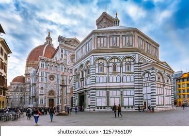 Florence, Italy - October 24, 2018: People on the square near historical medieval Duomo Santa Maria Del Fiore and Baptistery in old town, cloudy blue sky