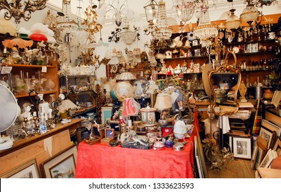 FLORENCE, ITALY - SEPT 25: Room full of old lamps, gold, toys, retro furniture in flea market with second hand staff on September 25, 2018. Near 87 percent of Florence population are Italian