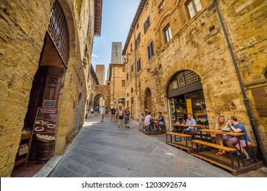 Florence, Italy - September 18, 2018: Tourists walking on Via San Matteo, medieval town of San Gimignano, Tuscany, Italy