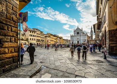 Florence, Italy - September 21 2016: Late summer afternoon in the Tuscan city of Florence Italy as crowds of tourists walk through Piazza Santa Croce towards the Basilica