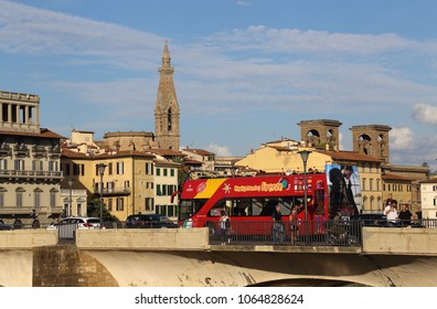 Florence, Italy - September 23, 2017: Bus with tourists crosses a bridge with in the background towers and historical buildings in Florence, Italy on September 23, 2017