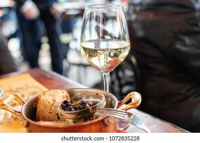 Florence, Tuscany / Italy. - April 20, 2018.  aperitif a glass of white wine and dark olives with pepper and bread, snacks are served in a copper pan on a wooden table.