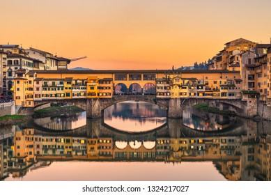 Florence, Tuscany, Italy - December 8, 2016: View of Ponte Vecchio at sunset. Old Bridge is a medieval stone closed-spandrel segmental arch bridge over the Arno River.