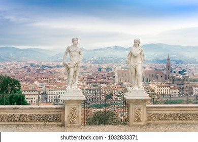 Florence, Tuscany / Italy - February 23, 2018. Two statues in the gardens of Villa Bardini and a view of the streets of Florence from a height, bright blue sky and terracotta roofs of houses
