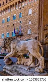 FLORENCE, TUSCANY, ITALY - March 31, 2019: Lion statue of Flaminio Vacca in the Loggia dei Lanzi and in the background Palazzo della Signoria in the historic center World Heritage Site.