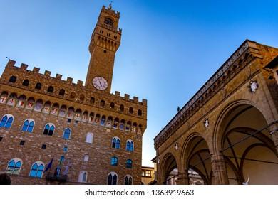 FLORENCE, TUSCANY, ITALY - March 31, 2019: View of the Palazzo della Signoria called Palazzo Vecchio and the vault of the Loggia dei Lanzi, in the historic center World Heritage Site.