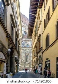 Florence, Tuscany, Italy. May 23, 2017: Typical narrow streets in the old part of Florence with people walking, in the background the Florence Duomo