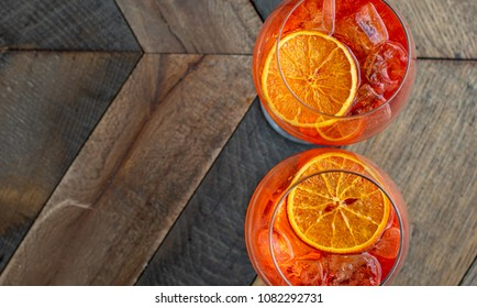 "Florence, Tuscany / Italy. - May 3, 2018. Classic Italian aperitif  ""aperol stpritz"" with ice and a slice of orange in t large round glass on a wooden table in a bar in Italy"