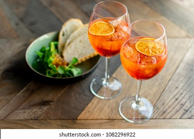 "Florence, Tuscany / Italy. - May 3, 2018. Classic Italian aperitif ""aperol stpritz"" with ice and a slice of orange with appetizers from the leaves of lettuce, pate and toasted bread"