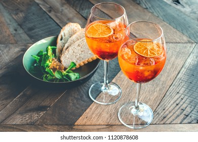 """Florence, Tuscany / Italy. - May 3, 2018. Classic Italian aperitif """"aperol stpritz"""" with ice and a slice of orange with ice and with appetize. glasses on a wooden table, selective focus and copy space"""
