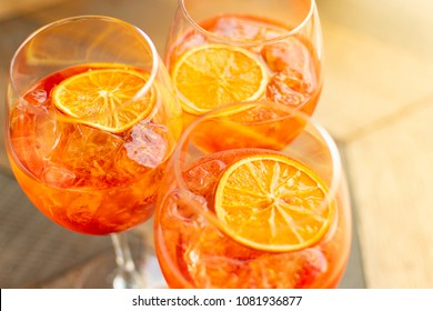 "Florence, Tuscany / Italy. - May 4, 2018. Italian aperitif  ""aperol stpritz"" with ice and a slice of orange in  large round glasses on a wooden table in a bar in Italy"