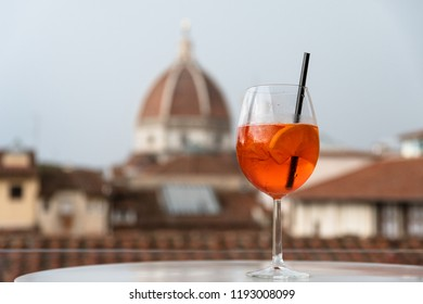 """Florence, Tuscany/ Italy. October 1, 2018. A glass of Italian cocktail """"aperol spritz"""" on the background of the Cathedral of Santa Maria del Fiore in the center of Florence. two symbols of Italy"""